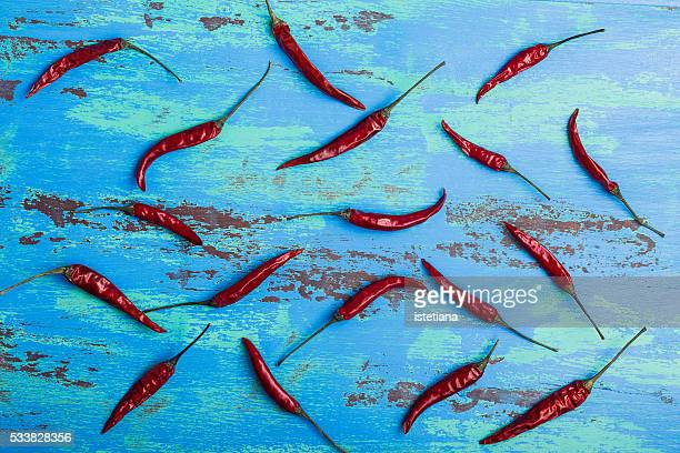 Red hot chili peppers on rustic blue wooden board, overhead view