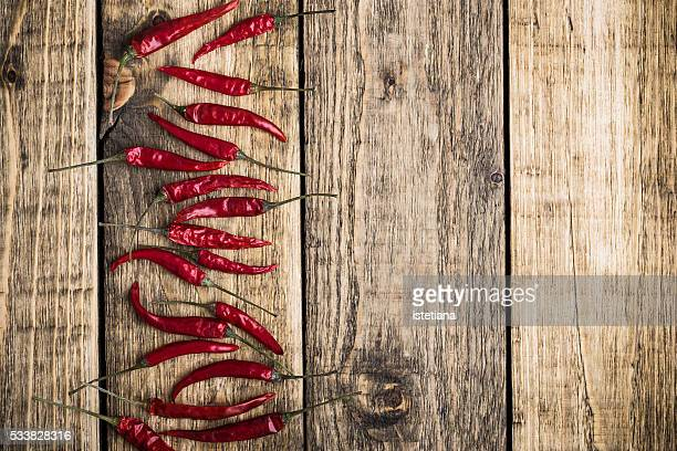 Red hot chili peppers on rustic wooden board with copy space, overhead view