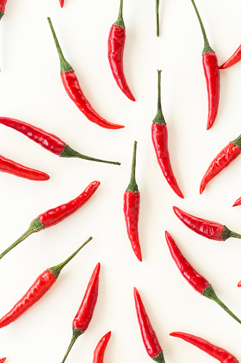 red hot chili peppers, popular spices concept - closeup isolated beautiful red hot chili peppers on white background, green tails, collage of freely lying peppers, top view, flat lay 675243278