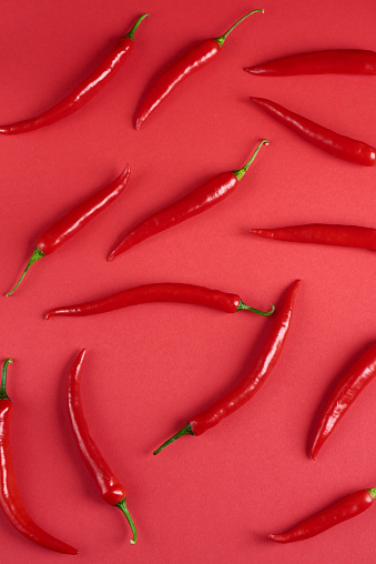 red hot chili peppers, popular spices concept - decorative pattern of red hot chili with green tails on red background, beautiful red collage of freely lying peppers, top view, flat lay 862047562