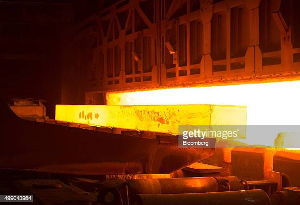 A red hot steel beam is extracted from a furnace ahead of processing at the Evraz Plc Consolidated WestSiberian Metallurgical Plant in Novokuznetsk...