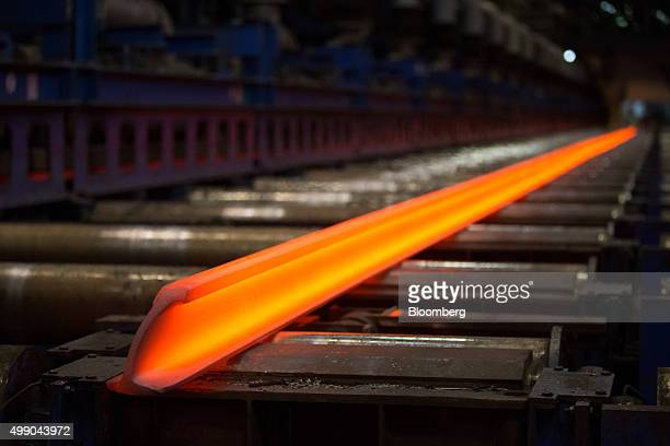 A red hot steel beam shaped into a hundred meter long train track rail lies on a rolling conveyor at the Evraz Plc Consolidated WestSiberian...