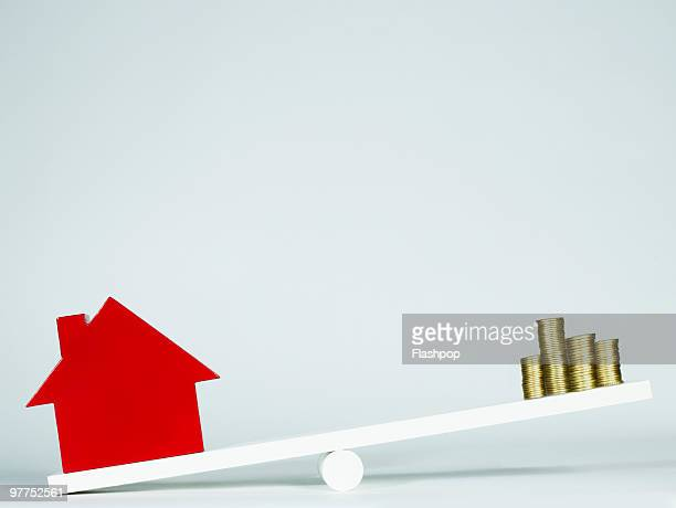Red house balancing on seesaw with stack of coins