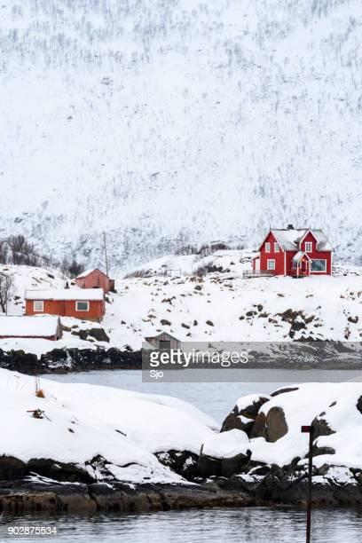Rode huizen op het eiland Senja in Noord Noorwegen in de winter
