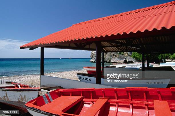 Red Hulled Boats Under a Red Roofed Boathouse