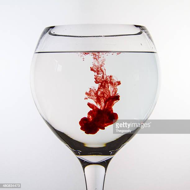 Red ink dissolving in glass of water