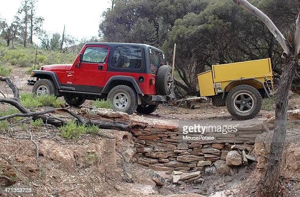 Red Jeep pulling yellow offroad trailer through Flinders Ranges