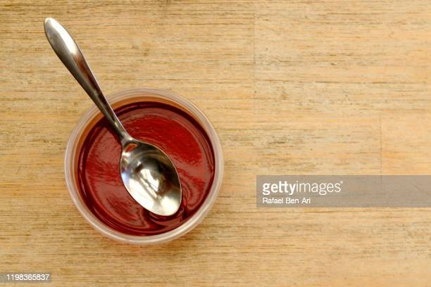 red jelly cup and a spoon - rafael ben ari stockfoto's en -beelden