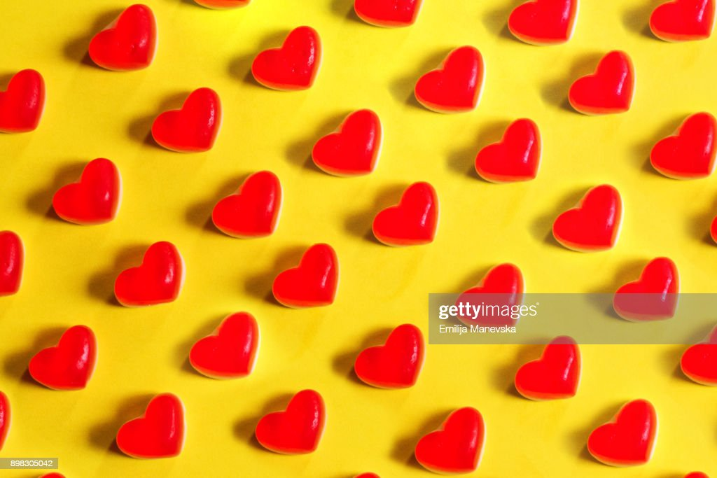 Red jelly heart shaped sweets on a yellow background : Stock Photo
