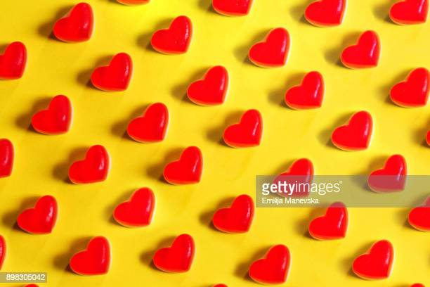 Red jelly heart shaped sweets on a yellow background