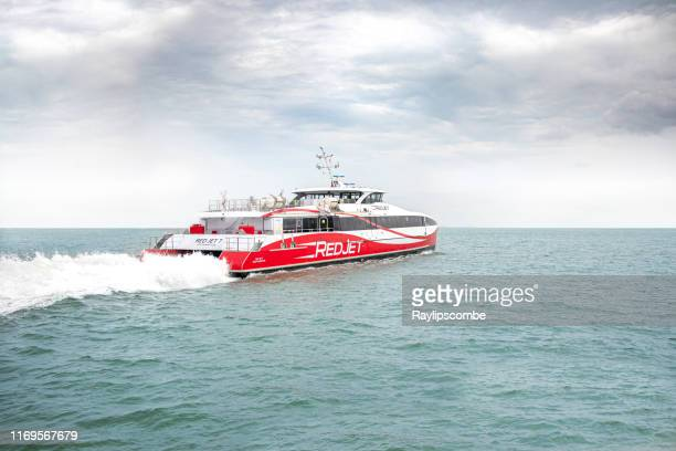red jet  hi-speed catamaran passenger ferry leaving the port of southampton on its way to the isle of wight - it provides a cross-solent ferry route between southampton & west cowes - passenger craft stock pictures, royalty-free photos & images