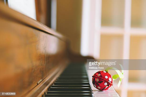 Red jingle bell with polka dots on piano keyboard