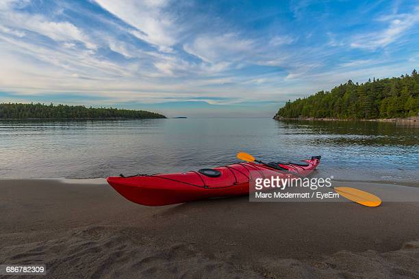 red kayak moored at lakeshore against cloudy sky - canoe stock pictures, royalty-free photos & images