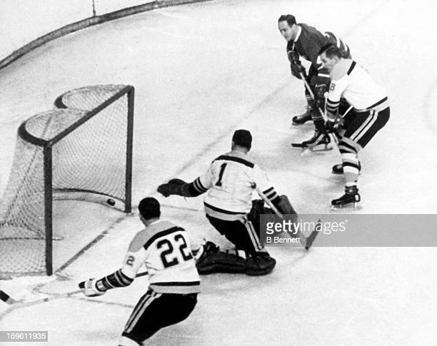 Red Kelly of the Toronto Maple Leafs scores on goalie Eddie Johnston of the Boston Bruins as Bob Woytowich of the Bruins and Bob Dillabough defend...