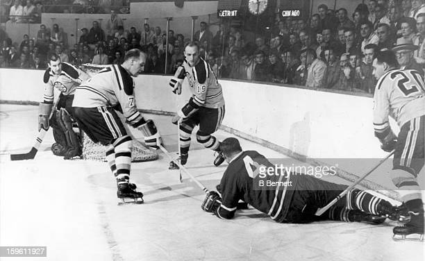 Red Kelly of the Toronto Maple Leafs tries to cover the puck as Cliff Pennington Doug Mohns and Leo Boivin of the Boston Bruins surround him as...