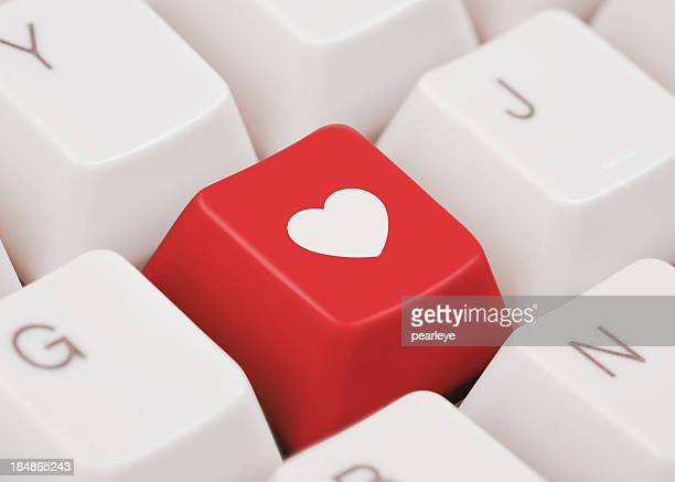 Red key with heart symbol on computer keyboard