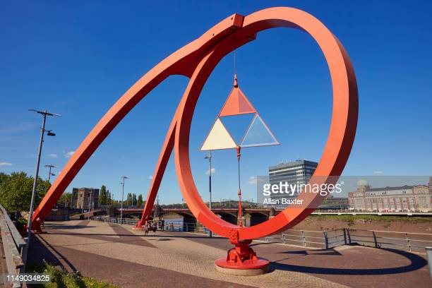 red kinetic 'steel wave' sculpture on the shoreline of the river usk, newport - newport wales photos stock pictures, royalty-free photos & images