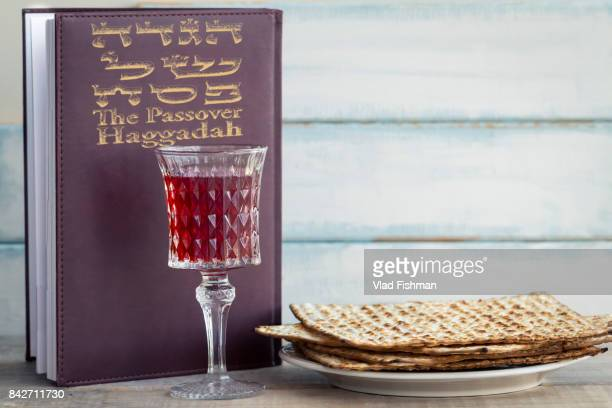 red kosher wine with a white plate of matzah or matza and a passover haggadah on a vintage wood background presented as a passover seder meal with copy space. - happy passover stock pictures, royalty-free photos & images