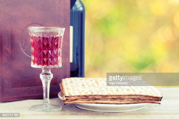 red kosher wine with a white plate of matzah or matza and a passover haggadah on a vintage wood background presented as a passover seder meal with copy space. - passover seder plate stock pictures, royalty-free photos & images