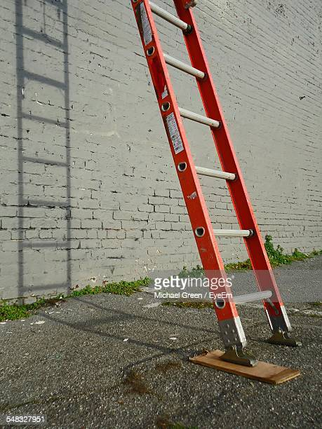 red ladder leaning against wall - step ladder stock pictures, royalty-free photos & images