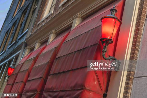 red lamp next to a red awning - 売春宿 ストックフォトと画像