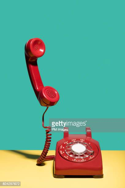 Red landline phone, receiver in mid air