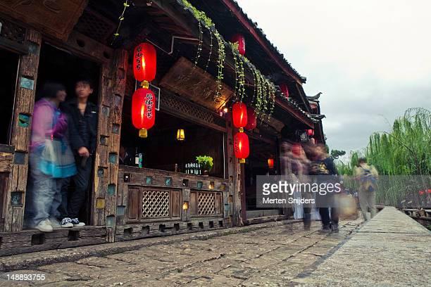 red lanterns and strolling people in old town street. - merten snijders stockfoto's en -beelden