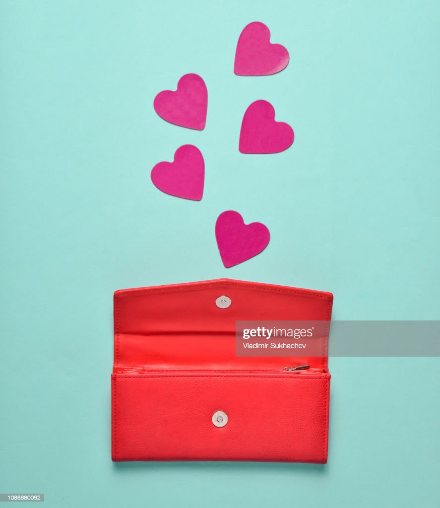 Red leather purse with decorative hearts on a blue pastel background, concept of love, minimalism : Stock Photo