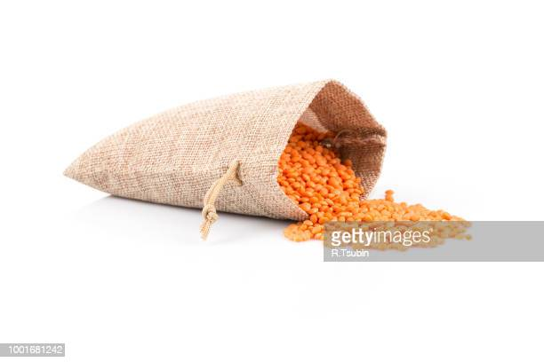 red lentils in burlap bag and heap of red lentils isolated on white background - lentil stock pictures, royalty-free photos & images