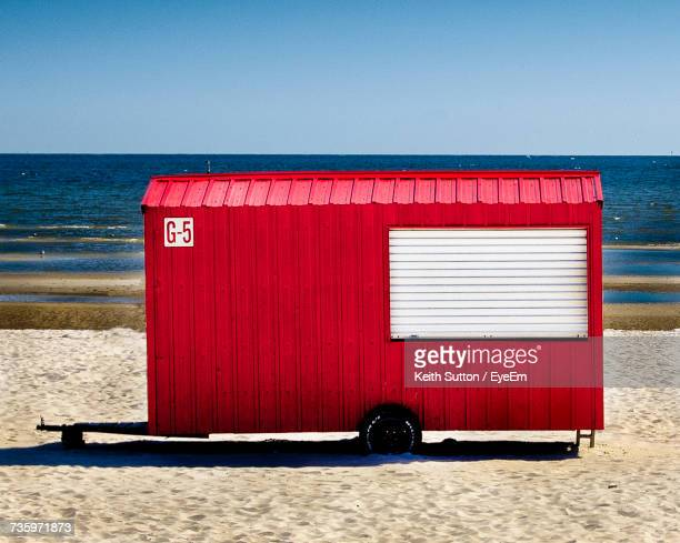 Red Lifeguard Hut On Beach Against Clear Sky