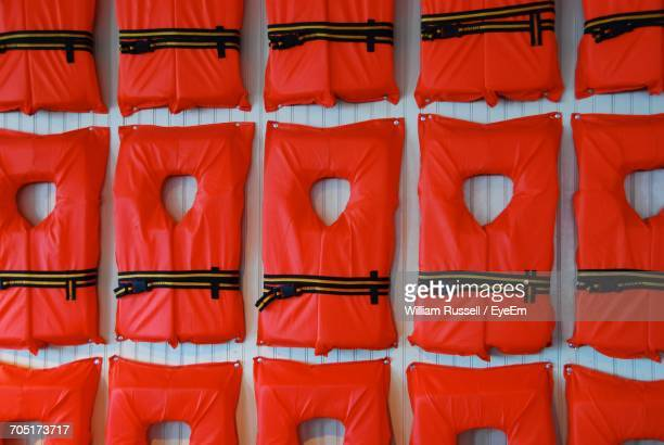 Red Lifevests Hanging On Wall