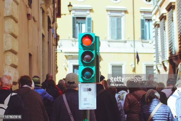 red light at a traffic light on a street full of tourists - semaphore stock pictures, royalty-free photos & images