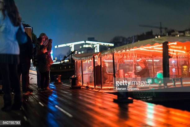 red light bar boat docked along amstel river - merten snijders stock-fotos und bilder