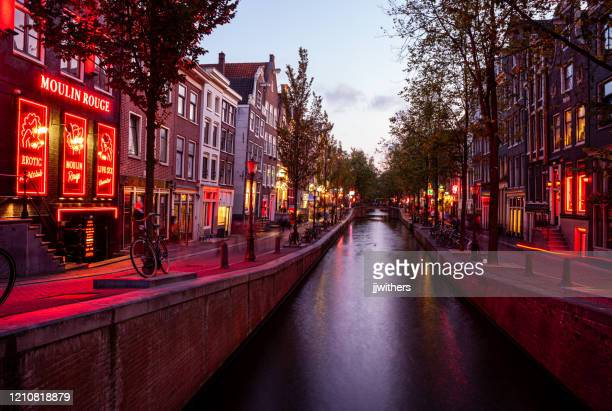 red light district along oudezijds achterburgwal street in amsterdamn netherlands at dusk/sunset. - red light district stock pictures, royalty-free photos & images
