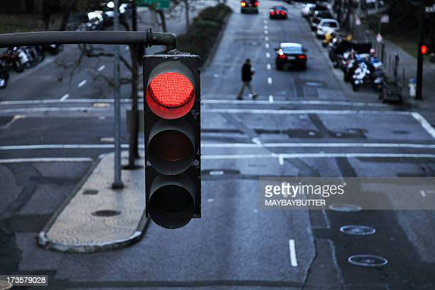 red light hanging above a paved street in the city - road signal stock pictures, royalty-free photos & images