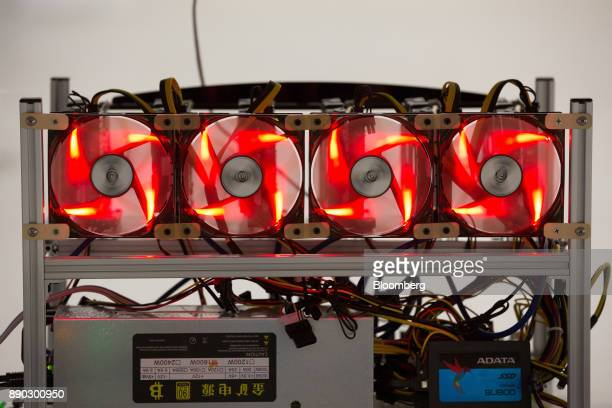 Red light illuminates cooling fans used to cool cryptocurrency mining rigs at the SberBit mining 'hotel' in Moscow Russia on Saturday Dec 9 2017...