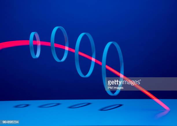red light streaking through 4 hoops - same action stock photos and pictures