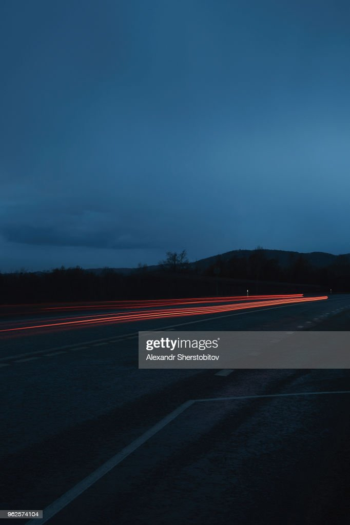 Red light trails on road against sky at night : Stock Photo