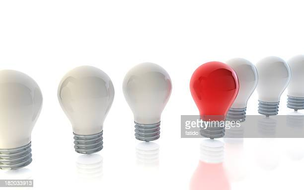 A red lightbulb standing out from crowd of white lightbulbs