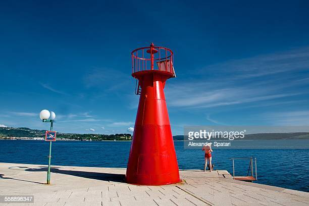red lighthouse and guy in red swimwear - young men in speedos stock pictures, royalty-free photos & images