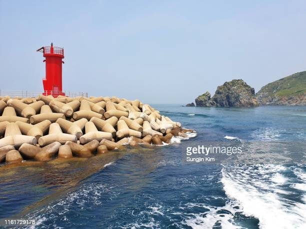 a red lighthouse at seawall - seawall stock pictures, royalty-free photos & images