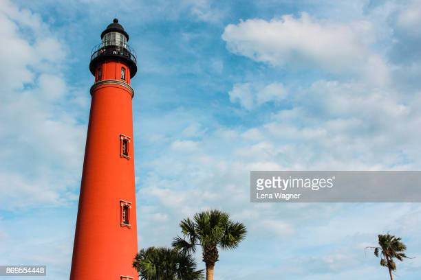 Red Lighthouse Towering Over Palm Trees