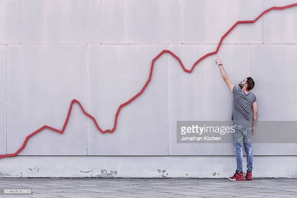 red line graph with man - wachstum stock-fotos und bilder
