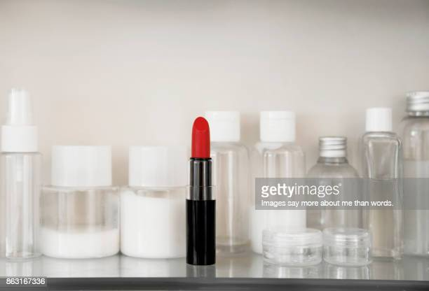 A red lipstick stands out on the shelf. Still life