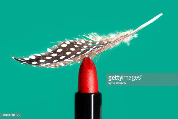 red lipstick with feather on mint green background. - damp lips stock pictures, royalty-free photos & images