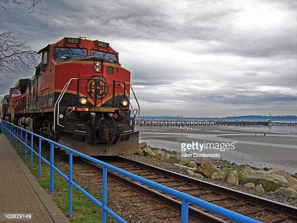 Red locomotive rumbling along the train tracks during low tide next to the shoreline and pier on an overcast day in White Rock, British Columbia...