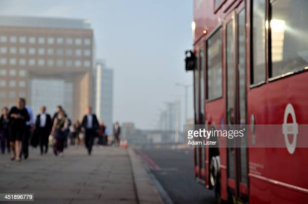 Red London Bus is seen crossing London Bridge in the misty morning Commuting Rush Hour. Suited commuters are walking to their City of London business...