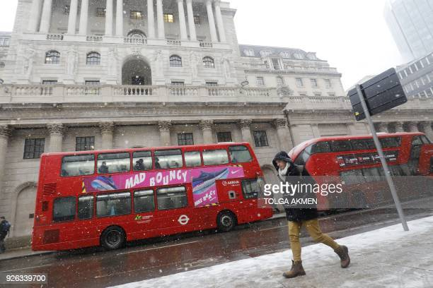 A red London bus makes it's way through the snow as a blizzard hits central London on March 2 2018 The Met Office has issued 10 severe weather...