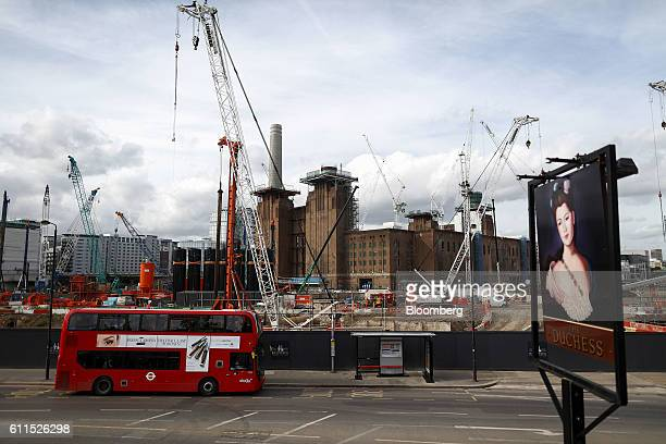 A red London bus passes construction cranes operating at the Battersea Power Station office retail and residential development which is backed by...
