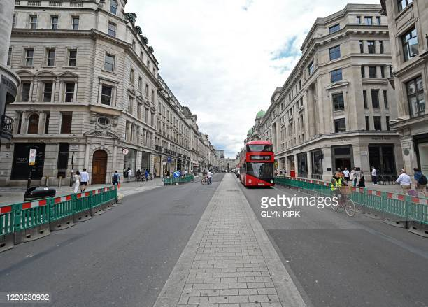 Red London bus travels down Regent Street in London, on June 15, 2020 as some non-essential retailers reopen from their coronavirus shutdown. -...